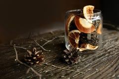 在一个玻璃瓶子、杉木锥体和干桔子 免版税图库摄影