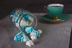 在一个玻璃瓶子和一个杯子的开胃甜自创蓝色和白色蛋白软糖在灰色背景的一块帆布 免版税库存图片