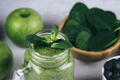 在一个玻璃瓶子和成份的健康绿色圆滑的人在白的菠菜、苹果和蓝莓 Superfood,戒毒所食物 免版税库存图片