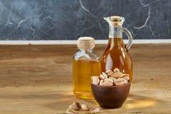 在一个玻璃瓶子和瓶的芳香油有在碗的pistacios的在木桌,特写镜头上 库存图片