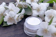 在一个玻璃瓶子的化妆奶油有在木背景的茉莉花花的 免版税库存照片