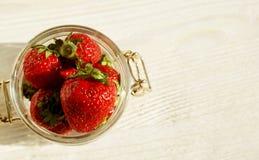 在一个玻璃瓶子的大红色甜草莓在一张木桌上 免版税库存图片
