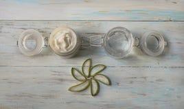 在一个玻璃瓶子的奶油色和自创芦荟维拉胶凝体,有在轻的木背景的被切开的芦荟叶子的 图库摄影