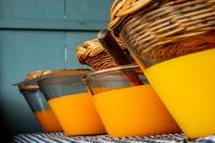 在一个玻璃瓶子的新鲜的橙汁有盒盖篮子的 图库摄影