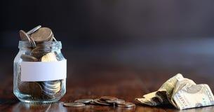 在一个玻璃瓶子的硬币在一个木地板上 从硬币的口袋储款 库存图片