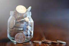 在一个玻璃瓶子的硬币在一个木地板上 从硬币的口袋储款 库存照片