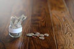 在一个玻璃瓶子的硬币在一个木地板上 从硬币的口袋储款 免版税库存图片