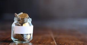 在一个玻璃瓶子的硬币在一个木地板上 从硬币的口袋储款 免版税库存照片