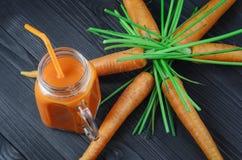 在一个玻璃瓶子的红萝卜汁用新鲜的红萝卜 免版税库存照片