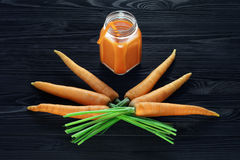 在一个玻璃瓶子的红萝卜汁用新鲜的红萝卜 库存照片
