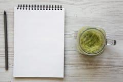 在一个玻璃瓶子的绿色芹菜圆滑的人,有铅笔的空白的笔记本在白色木表面,顶视图 r 免版税库存照片