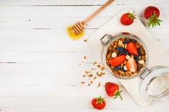 在一个玻璃瓶子的自创格兰诺拉麦片在一张白色桌上 健康的食物 库存照片