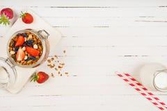 在一个玻璃瓶子的自创格兰诺拉麦片在一张白色桌上 健康的食物 免版税库存照片