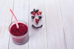 在一个玻璃瓶子的莓果圆滑的人有秸杆的,在葡萄酒木桌用新鲜的桑树莓果、黑莓和无核小葡萄干 微笑 库存照片