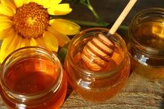 在一个玻璃瓶子的蜂蜜有在木地板上的花的 库存照片