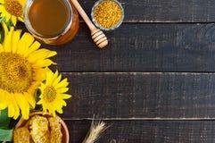 在一个玻璃瓶子的蜂蜜,蜂窝,花粉 养蜂业产品  免版税库存照片