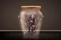 在一个玻璃瓶子里面的商人有闪电图画概念的 库存照片