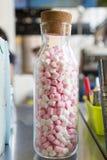 在一个玻璃瓶的替补糖桃红色有停止者的 库存图片