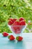 在一个玻璃碗的新鲜的草莓在被弄脏的自然背景的蓝色厨房用桌上 鲜美素食主义者夏天点心 库存图片