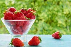 在一个玻璃碗的新鲜的草莓在被弄脏的自然背景的蓝色厨房用桌上 鲜美素食主义者点心 免版税库存图片