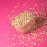 在一个玻璃碗的燕麦有桃红色的上色了背景 库存图片