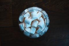 在一个玻璃碗的蛋白软糖在木背景 库存图片