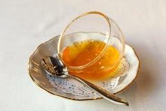 在一个玻璃花瓶的蜂蜜在有茶匙的白色板材 库存图片