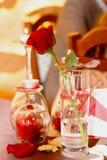 在一个玻璃近的蜡烛和玫瑰花瓣的浪漫一朵红色玫瑰在桌上 免版税图库摄影