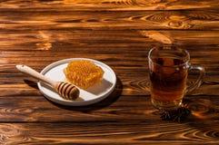 在一个玻璃透明杯子的黑芳香茶 白色板材用在木背景的金蜂蜜 复制空间 免版税库存照片
