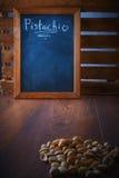 在一个瓢的开心果在一个棕色木地板上 文本的空白的黑委员会空间 免版税库存照片