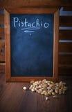 在一个瓢的开心果在一个棕色木地板上 文本的空白的黑委员会空间 库存照片