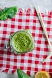 在一个瓶子杯子的顶视图健康绿色菠菜圆滑的人有在方格的餐巾的成份的在白色大理石桌上 有选择性 图库摄影
