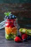 在一个瓶子的健康自创水果沙拉在土气木背景 健康食物,饮食、戒毒所或者素食主义者概念 库存照片