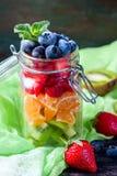 在一个瓶子的健康自创水果沙拉在土气木背景 健康食物,饮食、戒毒所或者素食主义者概念 免版税图库摄影