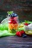 在一个瓶子的健康自创水果沙拉在土气木背景 健康食物,饮食、戒毒所或者素食主义者概念 免版税库存照片