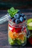 在一个瓶子的健康自创水果沙拉在土气木背景 健康食物,饮食、戒毒所或者素食主义者概念 图库摄影