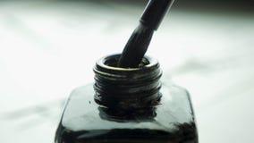 在一个瓶子的女性手扣篮刷子画的关闭的墨水  与选择聚焦的中国古板的画笔 库存照片
