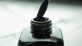 在一个瓶子的女性手扣篮刷子画的关闭的墨水  与选择聚焦的中国古板的画笔 免版税图库摄影
