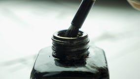 在一个瓶子的女性手扣篮刷子画的关闭的墨水  与选择聚焦的中国古板的画笔 免版税库存图片