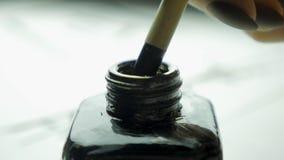 在一个瓶子的女性手扣篮刷子画的关闭的墨水  与选择聚焦的中国古板的画笔 免版税库存照片