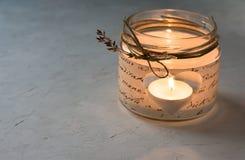 在一个瓶子的手工制造蜡烛台有纸decoupage的,心形的孔,灼烧的茶光,麻线,干燥花枝杈,华伦泰 免版税库存照片