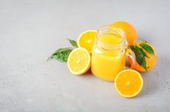 在一个瓶子的新鲜的橙汁过去在灰色具体背景 库存照片