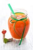 在一个瓶子的新鲜的红萝卜汁有两心脏的 橙色和绿色心脏晒衣夹 汁液 库存照片