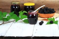 在一个瓶子的新鲜的自创黑莓果酱在白色木桌上 免版税库存照片