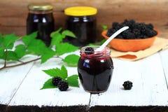 在一个瓶子的新鲜的自创黑莓果酱在白色木桌上 图库摄影