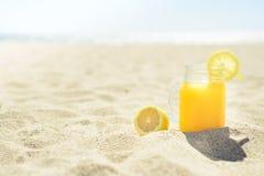 在一个瓶子的汁液在海滩 免版税库存照片