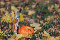 在一个瓶子的油漆刷黄色叶子和南瓜 免版税库存图片