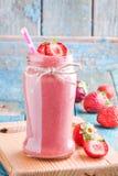 在一个瓶子的草莓圆滑的人有秸杆的 图库摄影