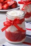在一个瓶子的草莓酸奶有弓垂直的 免版税库存图片