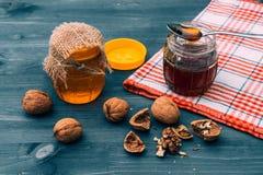 在一个瓶子的蜂蜜用在一张蓝色木桌上的核桃 在壳的核桃 图库摄影